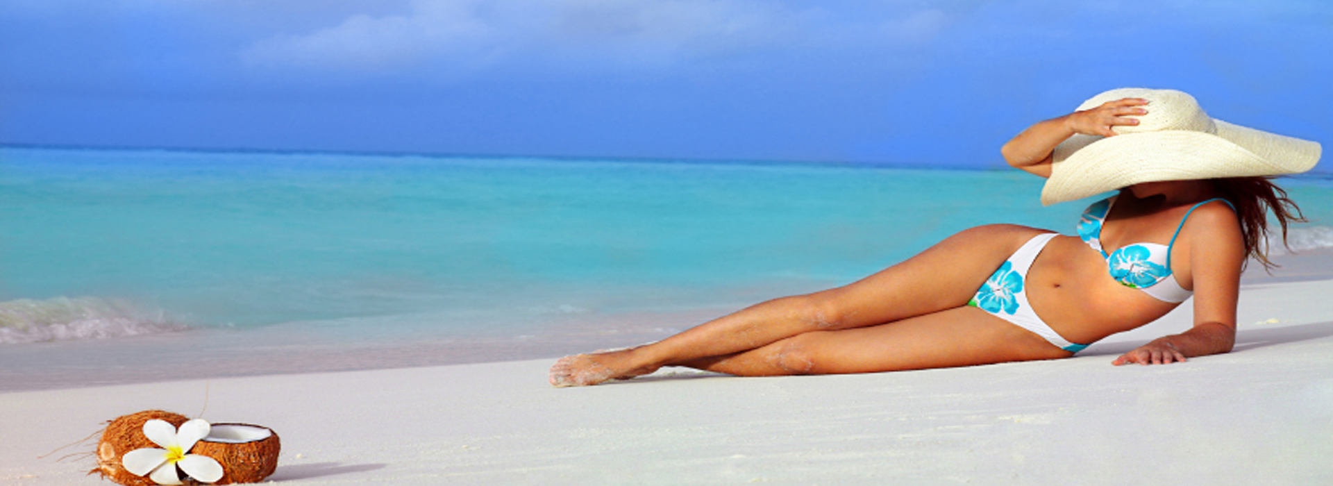 Picture of a woman lying on the sand at the beach.